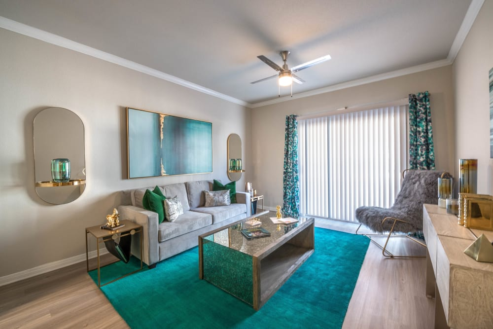Ceiling fan and hardwood flooring in a model apartment's living area at Olympus Town Center in Keller, Texas