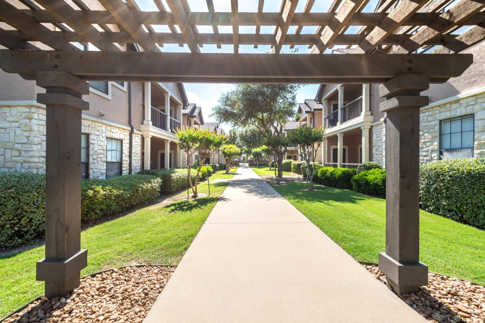 Pergola over a walkway between resident buildings at Olympus Town Center in Keller, Texas