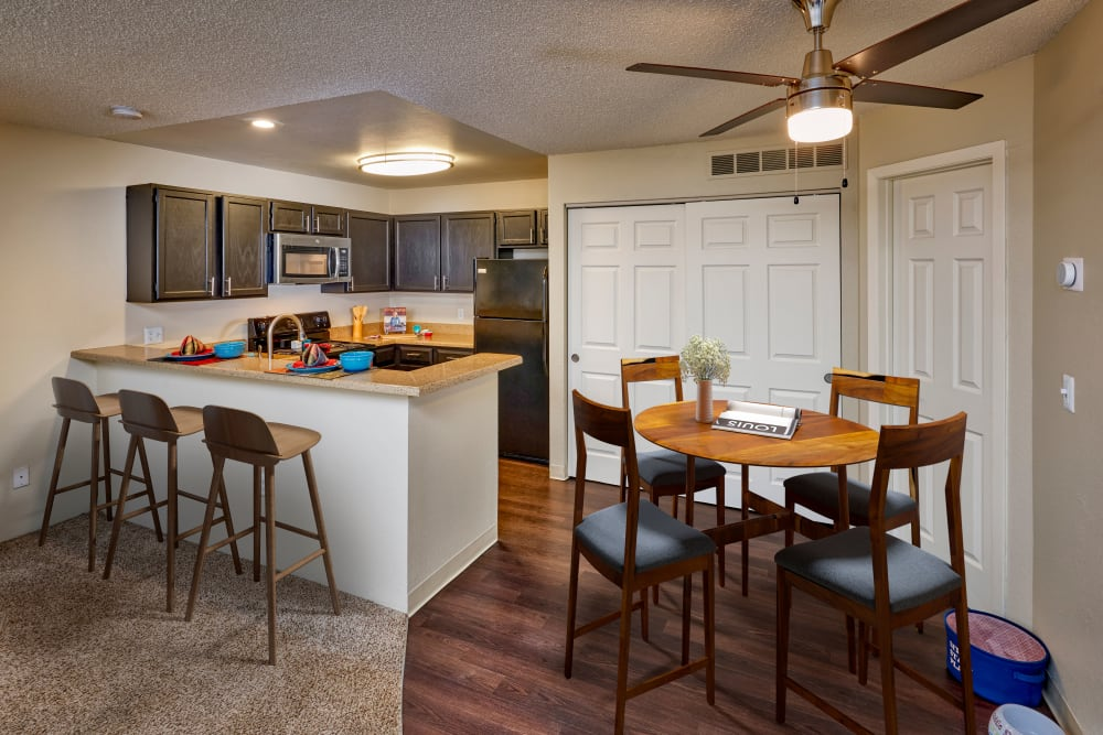 Kitchen with brown cabinets and a stacked washer and dryer at Bluesky Landing Apartments in Lakewood, Colorado
