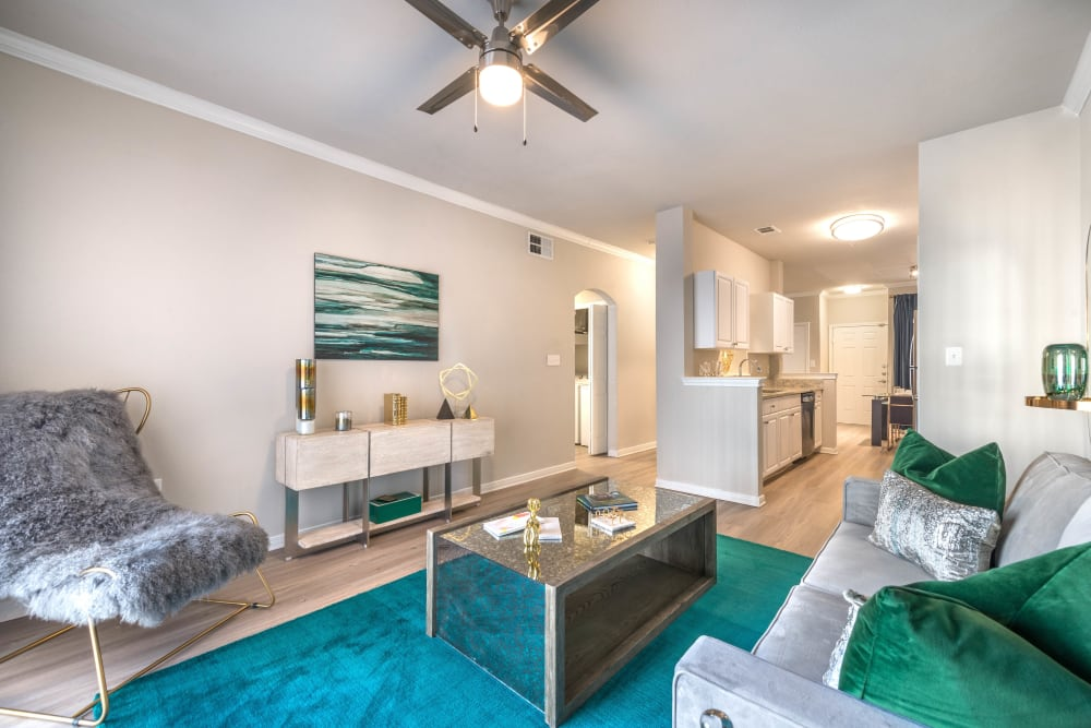 Modern furnishings and a ceiling fan in the living area of a model apartment at Olympus Town Center in Keller, Texas