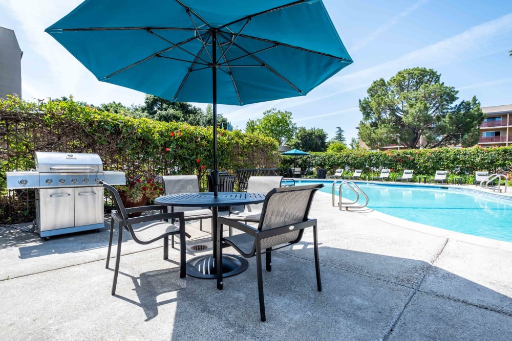 Outdoor pool, patio table with chairs and umbrella at Waterstone Fremont in Fremont, California