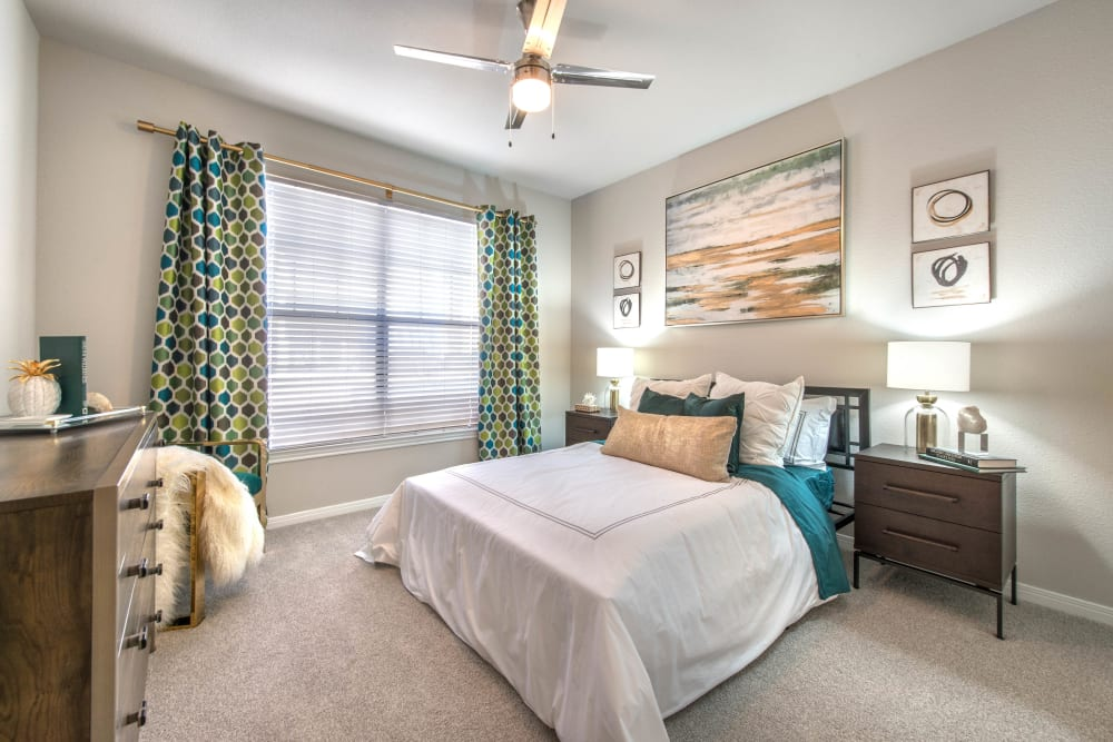 Plush carpeting and draped bay windows in a model home's bedroom at Olympus Town Center in Keller, Texas