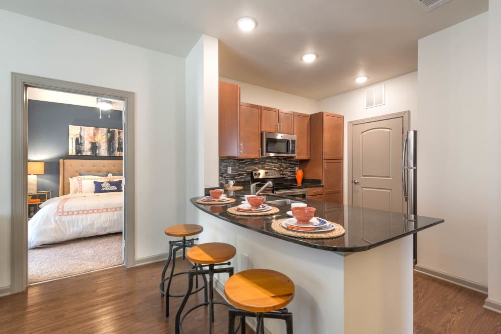 Model home's kitchen with an island and granite countertops at Olympus Waterford in Keller, Texas