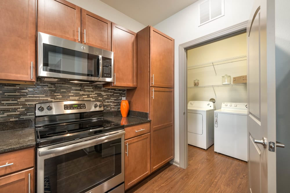 Sleek stainless-steel appliances and adjacent laundry room in a model home's kitchen at Olympus Waterford in Keller, Texas