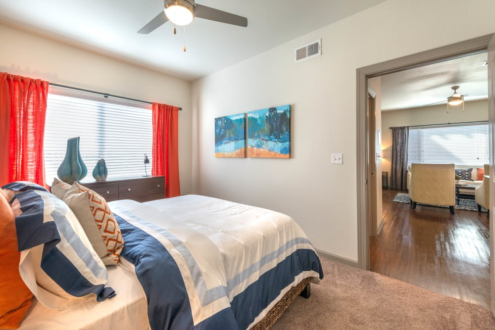 Draped windows and a ceiling fan in a model home's bedroom at Olympus Waterford in Keller, Texas