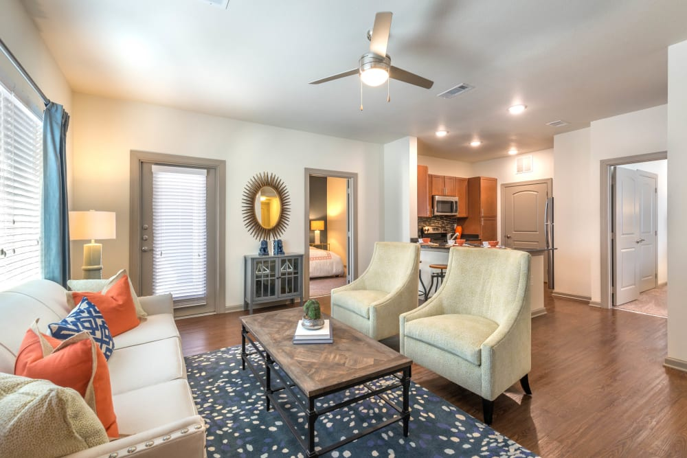 Ceiling fan and hardwood floors in the living area of a model apartment at Olympus Waterford in Keller, Texas