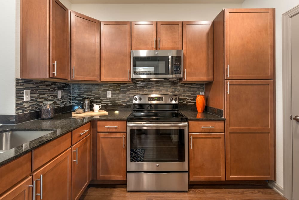 Cherry wood cabinetry and stainless-steel appliances in a model home's kitchen at Olympus Waterford in Keller, Texas