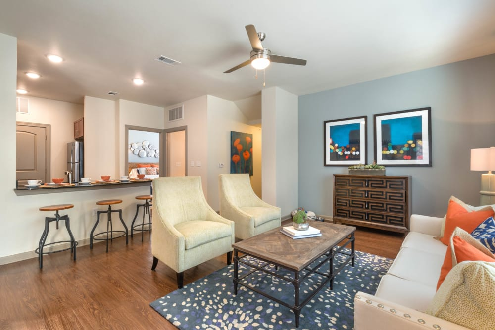 Well-furnished living area with a view of the kitchen's breakfast bar in a model home at Olympus Waterford in Keller, Texas