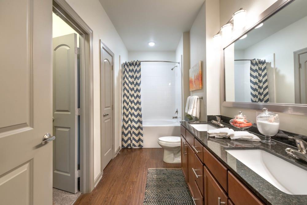 Dual sinks and a granite countertop in a model apartment's bathroom at Olympus Waterford in Keller, Texas