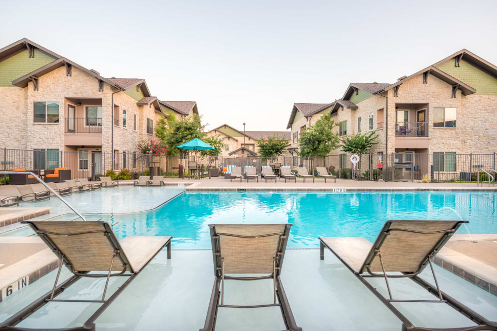 Lounge chairs in the swimming pool's sun deck at Olympus Waterford in Keller, Texas