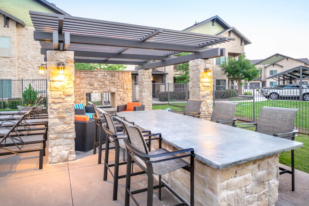 Barbecue area with bar seating at Olympus Waterford in Keller, Texas
