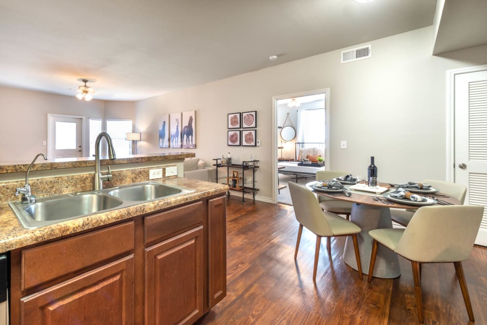 Spacious open-concept kitchen with a view of the living areas in a model apartment at Olympus Willow Park in Willow Park, Texas
