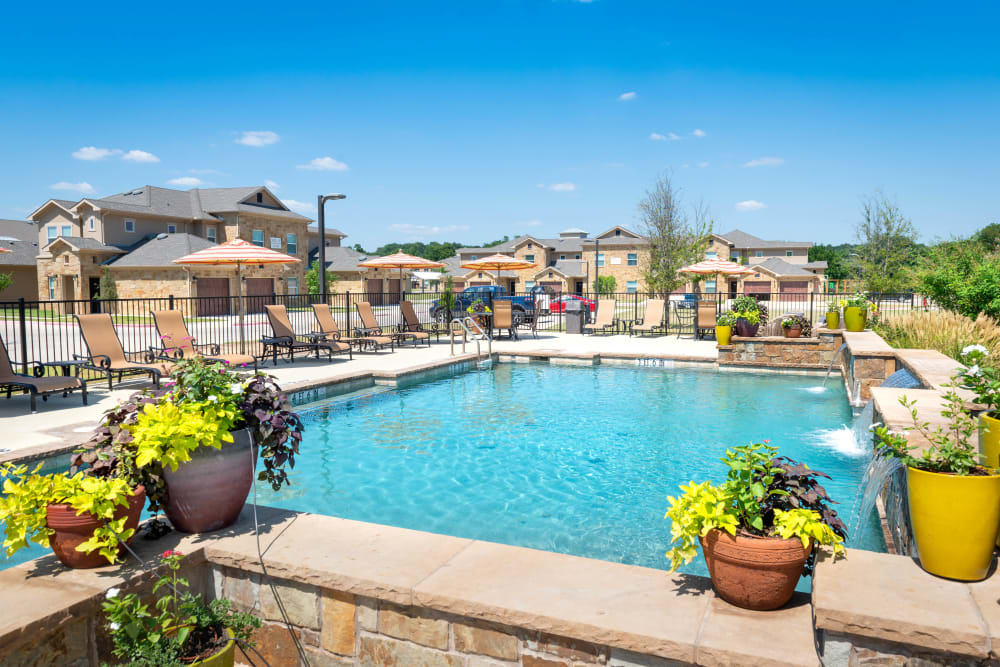 Resort-style swimming pool surrounded by professionally maintained flora at Olympus Willow Park in Willow Park, Texas