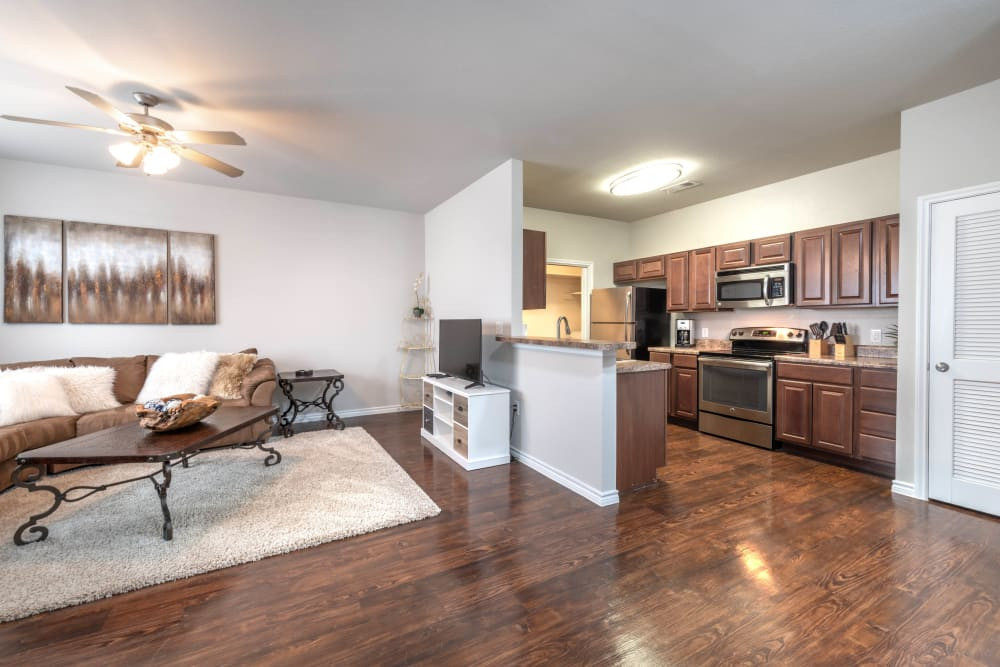 Beautiful hardwood floors throughout the living areas of a model apartment at Olympus Willow Park in Willow Park, Texas