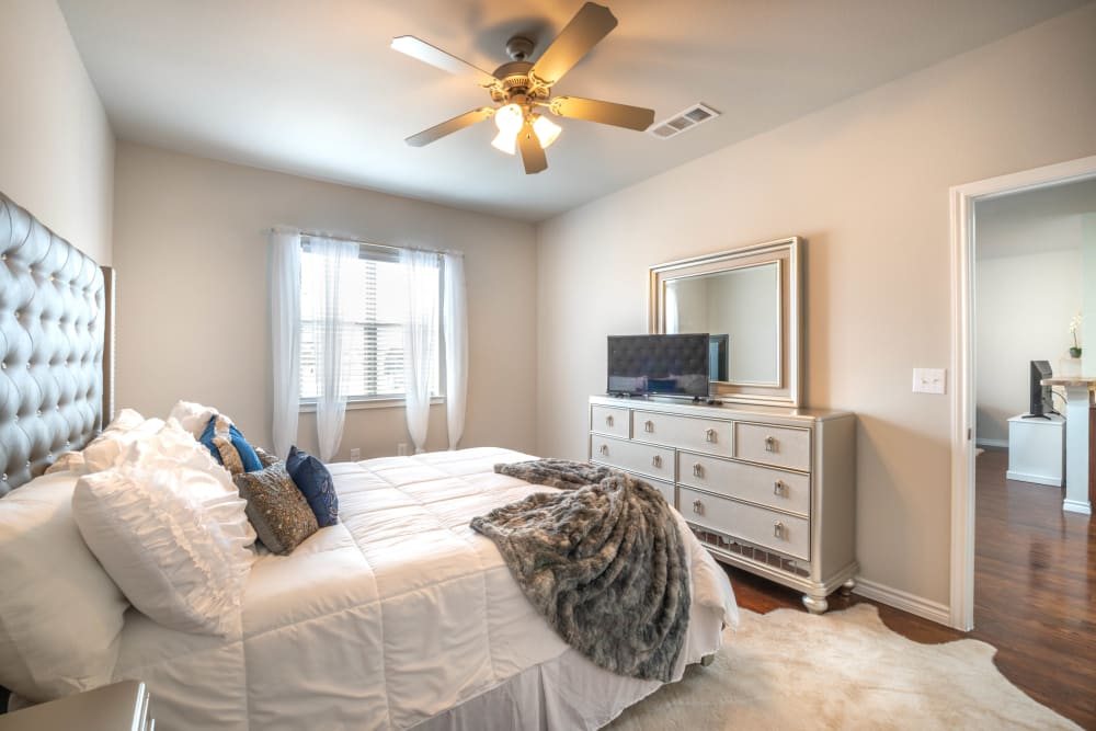 Well-furnished model home's bedroom with a ceiling fan at Olympus Willow Park in Willow Park, Texas