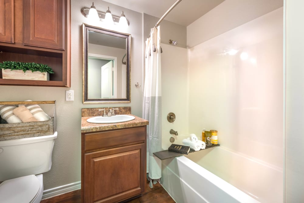 Model home's bathroom with a tiled shower and cherry wood cabinetry at Olympus Willow Park in Willow Park, Texas