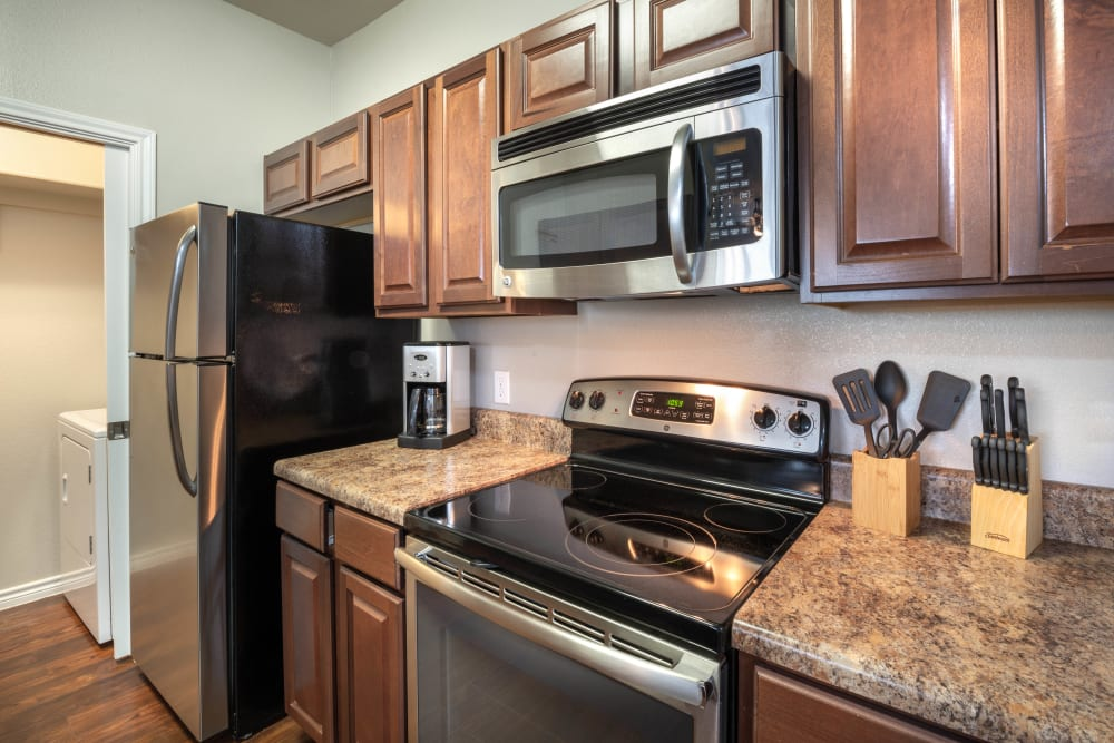 Granite countertops and stainless-steel appliances in a model home's kitchen at Olympus Willow Park in Willow Park, Texas