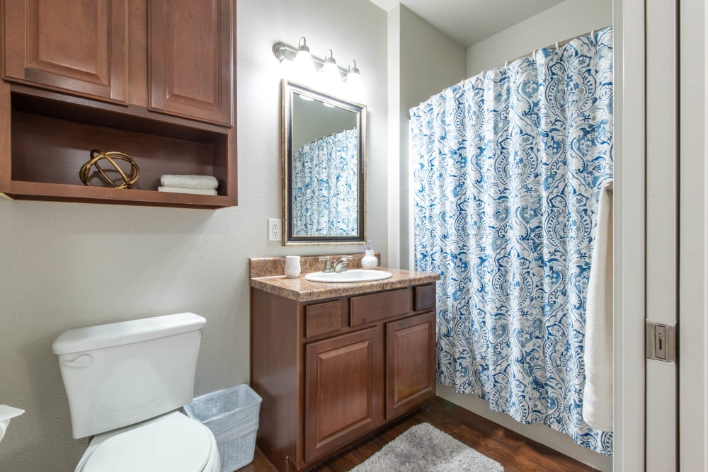 Cherry wood cabinetry in a model home's bathroom at Olympus Willow Park in Willow Park, Texas