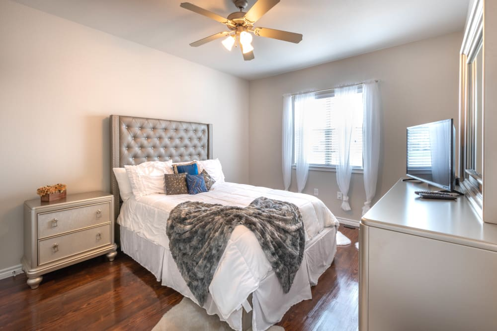 Ceiling fan and draped windows in a model home's bedroom at Olympus Willow Park in Willow Park, Texas