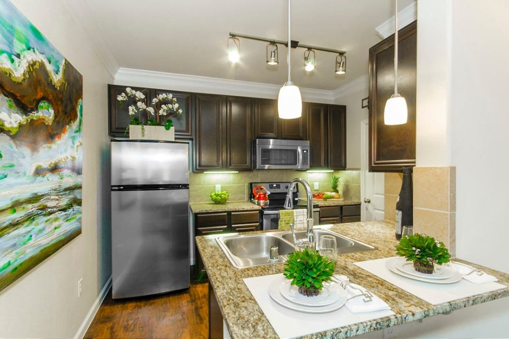 Gourmet kitchen with granite countertops in a model home at Olympus Woodbridge in Sachse, Texas