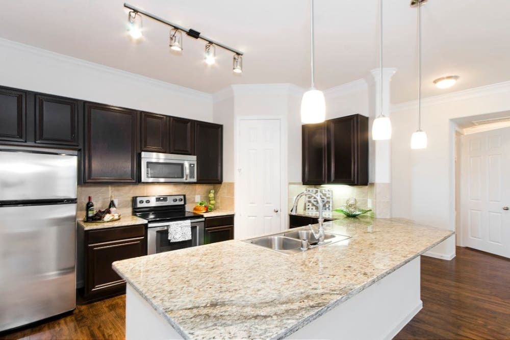 Granite countertops in a model home's kitchen at Olympus Woodbridge in Sachse, Texas