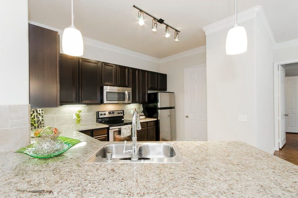 Expansive granite countertops in a model townhome's gourmet kitchen at Olympus Woodbridge in Sachse, Texas