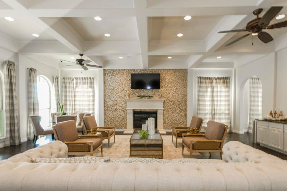 Luxurious resident clubhouse lounge in front of the fireplace at Olympus Woodbridge in Sachse, Texas