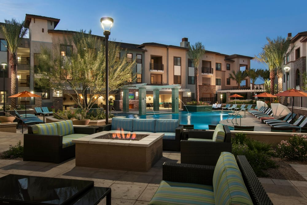 Resort-style swimming pool area and fire pit at dusk at Redstone at SanTan Village in Gilbert, Arizona