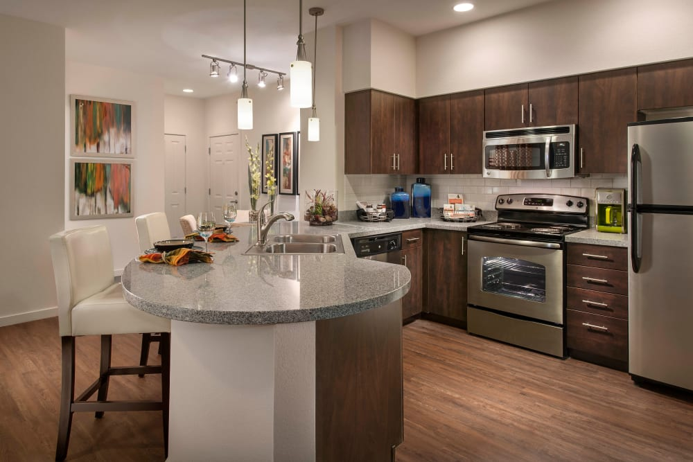 Rich wood cabinetry in a model home's gourmet kitchen at Redstone at SanTan Village in Gilbert, Arizona