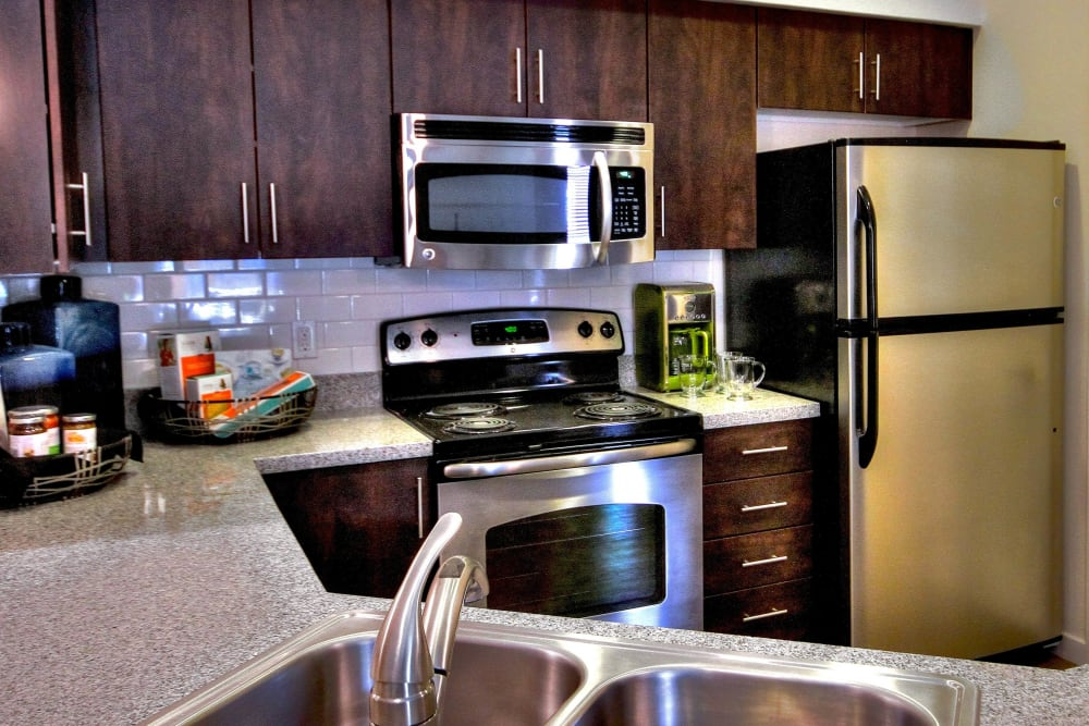 Rich, dark wood cabinetry in a model home's kitchen at Redstone at SanTan Village in Gilbert, Arizona