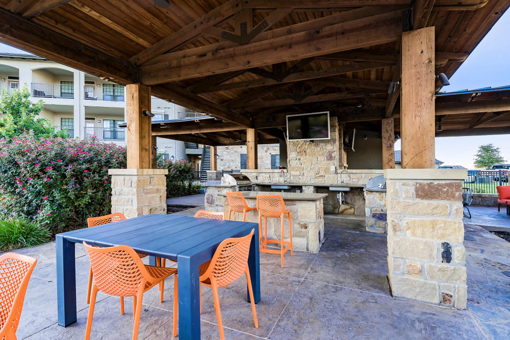 Covered barbecue area with a flatscreen TV and ample seating at Sedona Ranch in Odessa, Texas