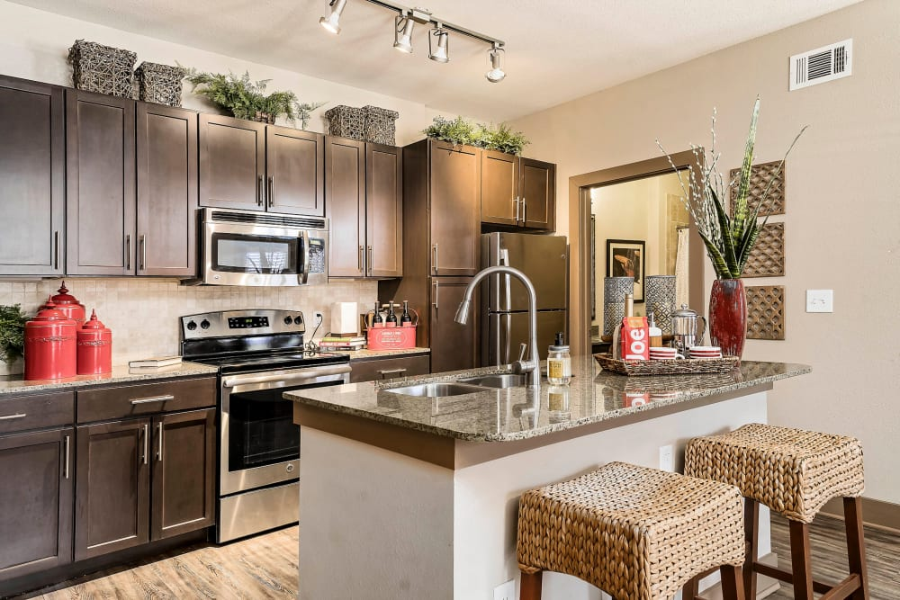Gourmet kitchen with granite countertops and an island in a model home at Sedona Ranch in Odessa, Texas