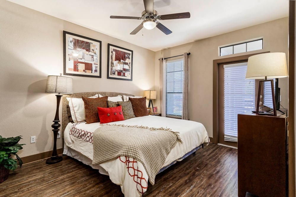 Ceiling fan and beautiful hardwood flooring in a model home's bedroom at Sedona Ranch in Odessa, Texas