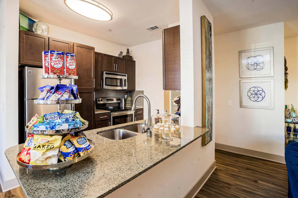 Model home's kitchen with breakfast bar and granite countertops at Sundance Creek in Midland, Texas