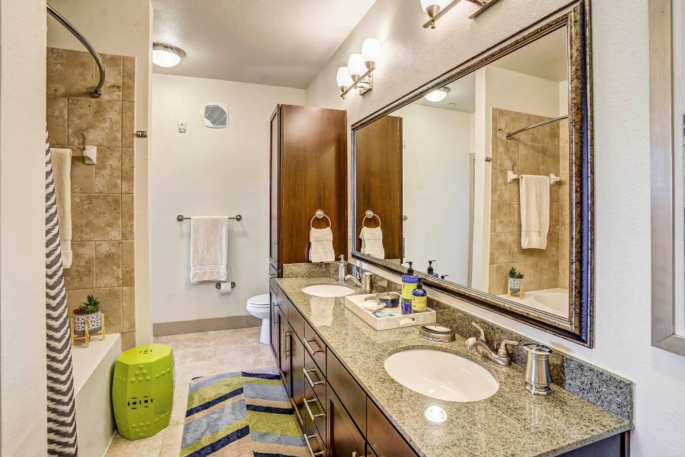 Oversized vanity mirror and a granite countertop in a model home's bathroom at Sundance Creek in Midland, Texas