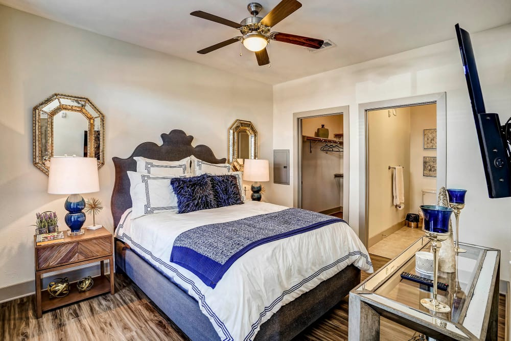 Well-furnished master bedroom with an en suite bathroom in a model apartment at Sundance Creek in Midland, Texas
