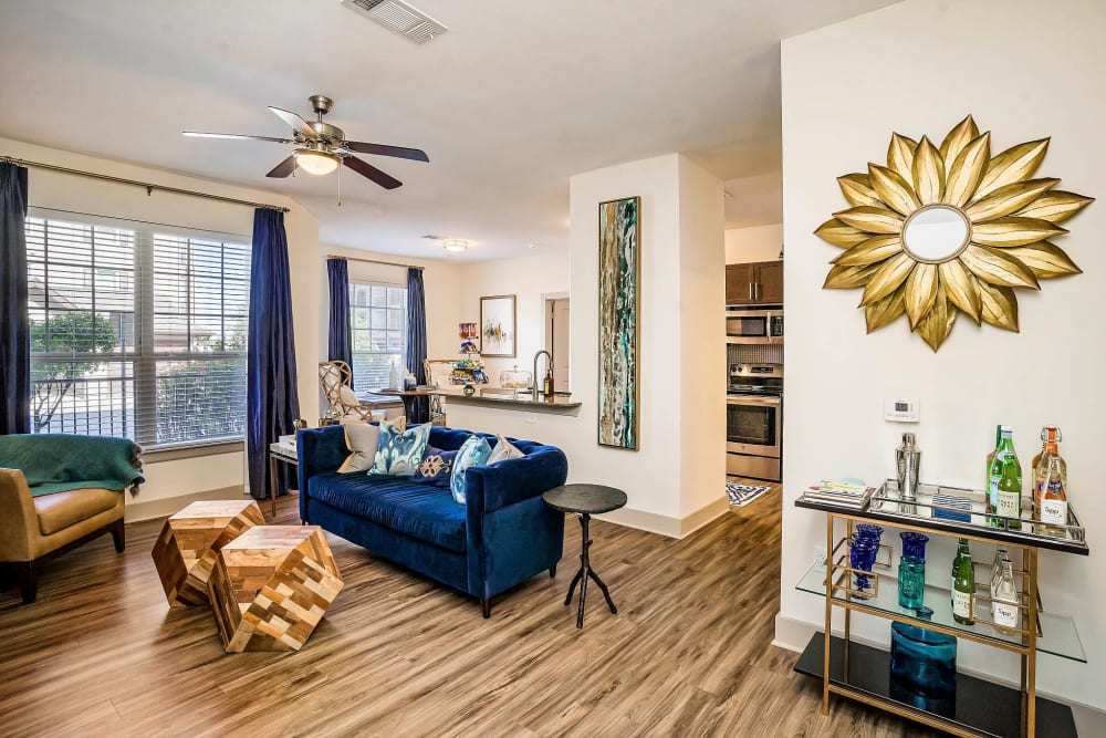 Hardwood floors and a ceiling fan in a model apartment's living area at Sundance Creek in Midland, Texas