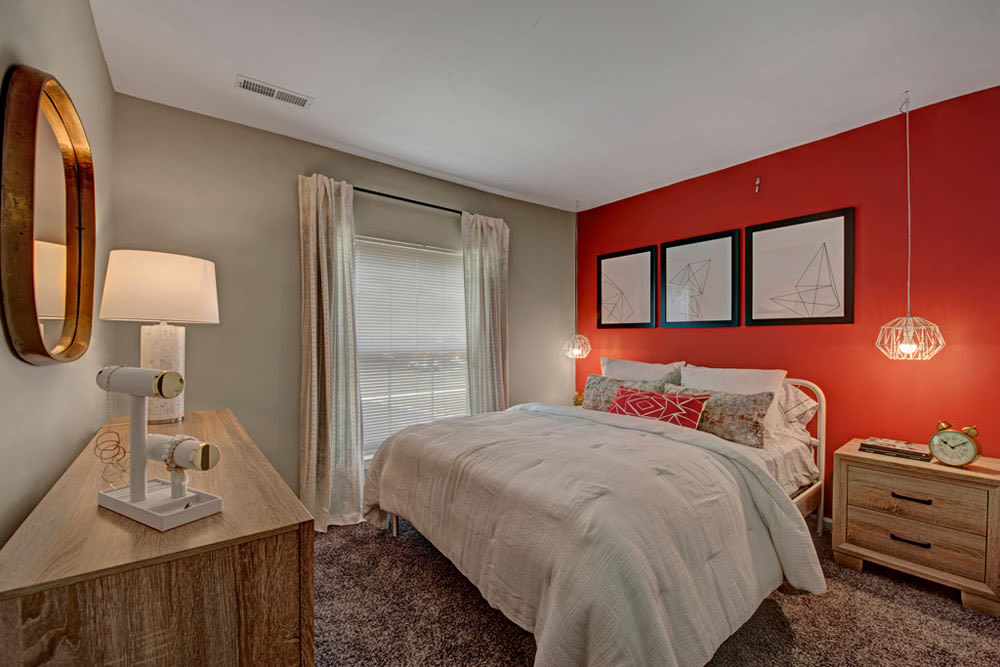 This spacious bedroom at Howard Crossing in Ellicott City, Maryland features a red colored accent wall and unique furnishings