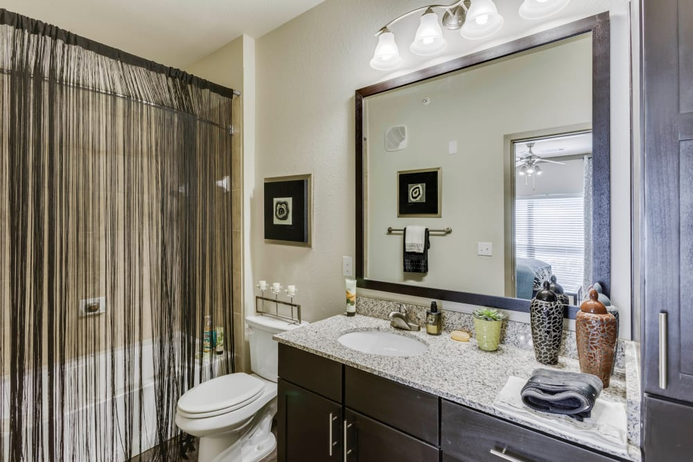 Large vanity mirror and a granite countertop in a model home's bathroom at Tacara at Westover Hills in San Antonio, Texas