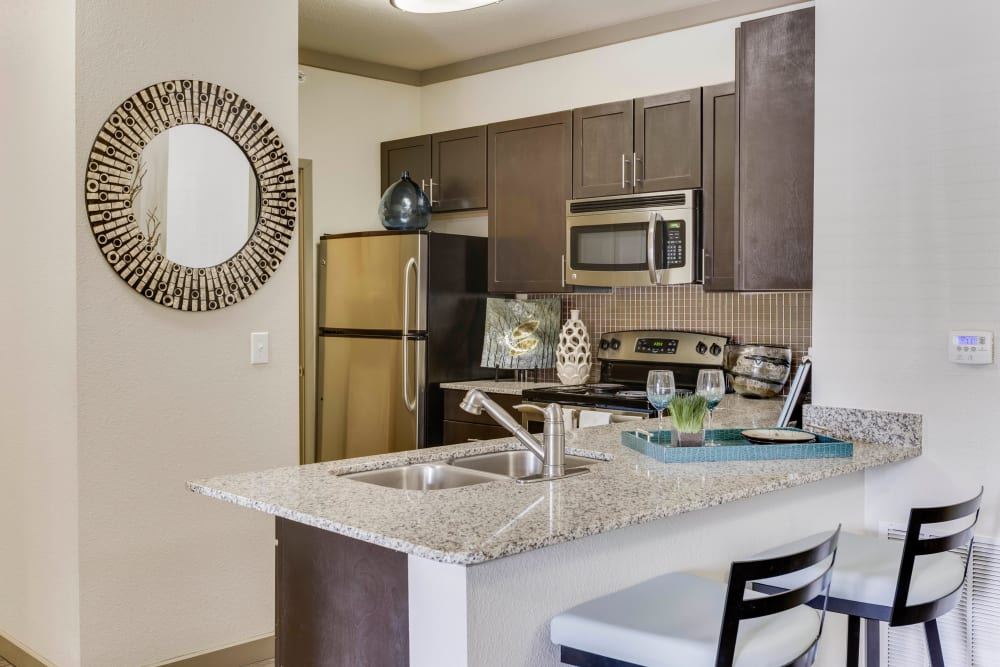 Stainless-steel appliances and a breakfast bar in a model home's kitchen at Tacara at Westover Hills in San Antonio, Texas