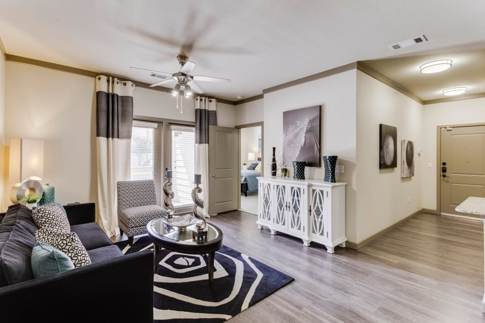 Well-furnished living area with a ceiling fan in a model home at Tacara at Westover Hills in San Antonio, Texas