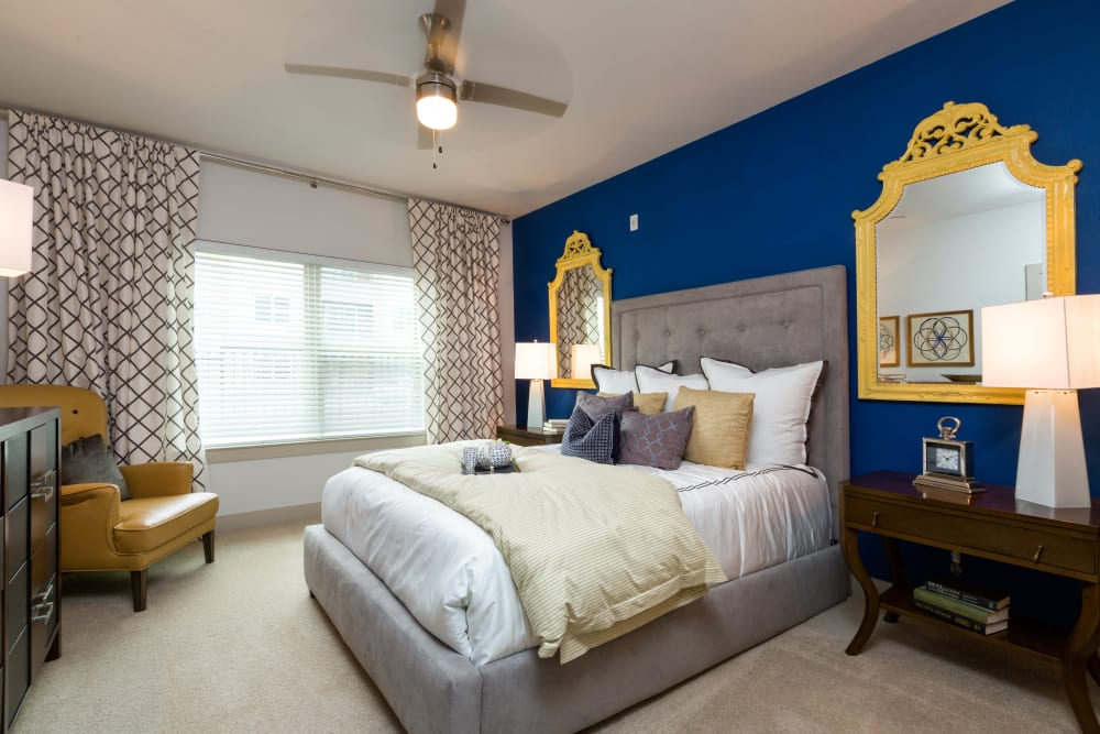 Well-furnished master bedroom with an accent wall in a model home at The Davis in Fort Worth, Texas