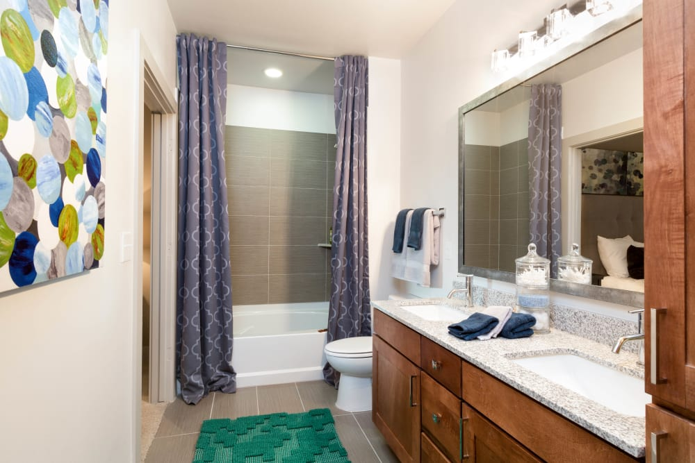 Custom tiled shower and a large vanity mirror in a model home's master bathroom at The Davis in Fort Worth, Texas
