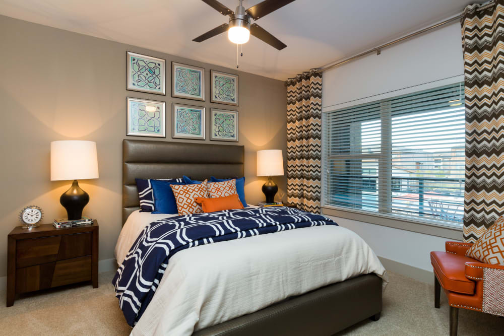 Well-furnished master bedroom with a ceiling fan in a model home at The Davis in Fort Worth, Texas