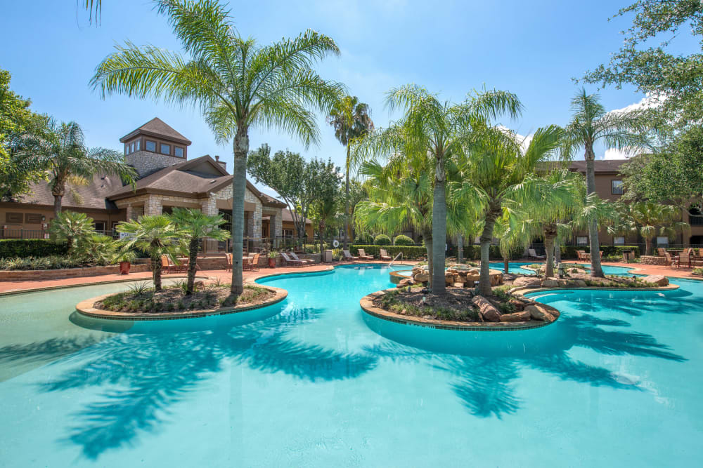 Resort-style swimming pool with islands and palm trees at The Ranch at Shadow Lake in Houston, Texas