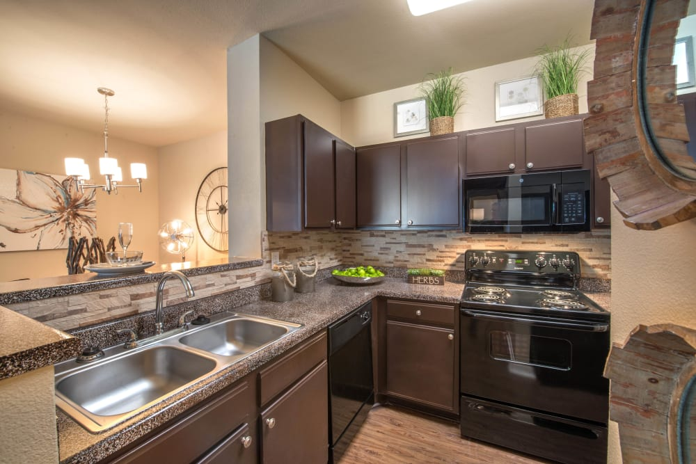 Dark wood cabinetry and sleek black appliances in a model apartment's kitchen at The Ranch at Shadow Lake in Houston, Texas