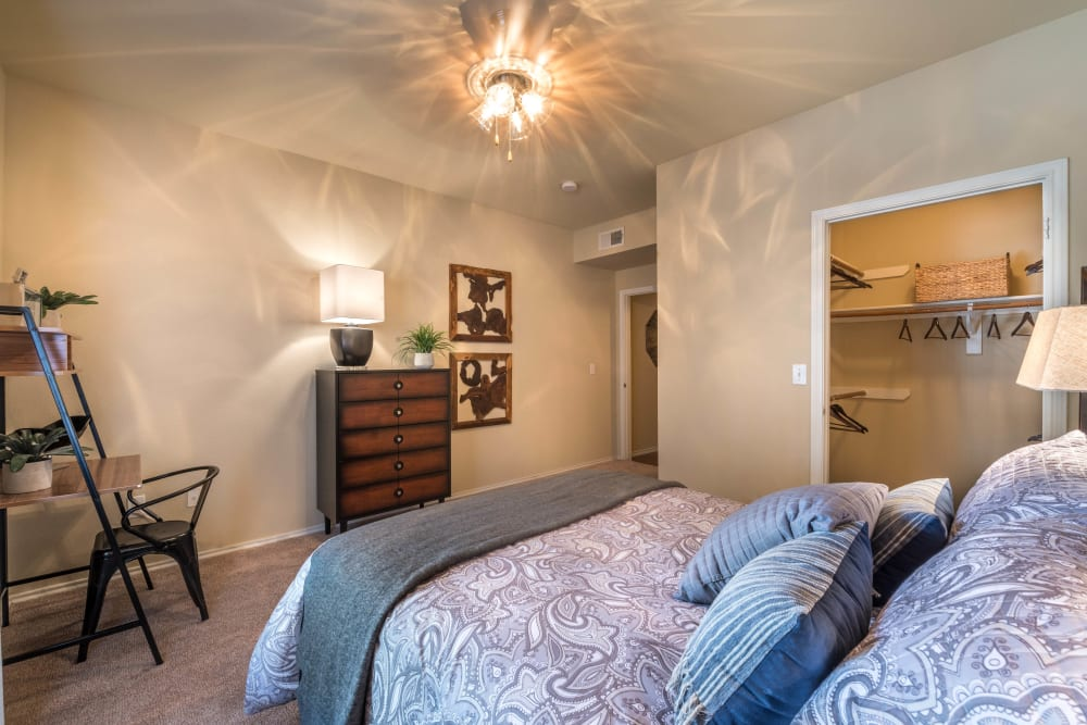 Walk-in closet and a ceiling fan in a model home's master bedroom at The Ranch at Shadow Lake in Houston, Texas