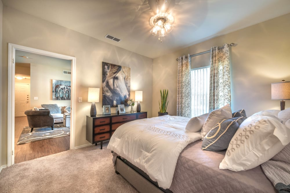 Large and well-furnished master bedroom with plush carpeting in a model home at The Ranch at Shadow Lake in Houston, Texas
