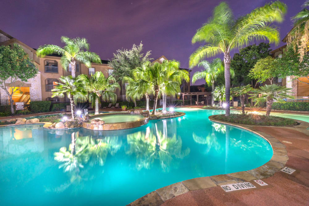 Resort-style swimming pool area brightly illuminated at dusk at The Ranch at Shadow Lake in Houston, Texas