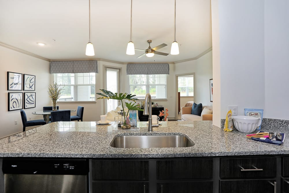 Large kitchen island with a granite countertop overlooking the living area in a model apartment at The Slate in Savannah, Georgia